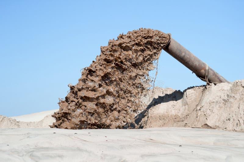 Flödet av brun flytande från röret på bakgrunden av en hög av sand och blå klar himmel royaltyfria foton