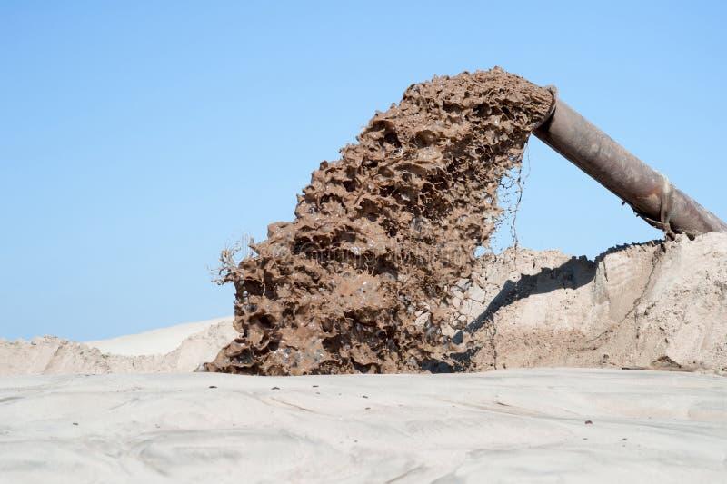 Flödet av brun flytande från röret på bakgrunden av en hög av sand och blå klar himmel royaltyfria bilder