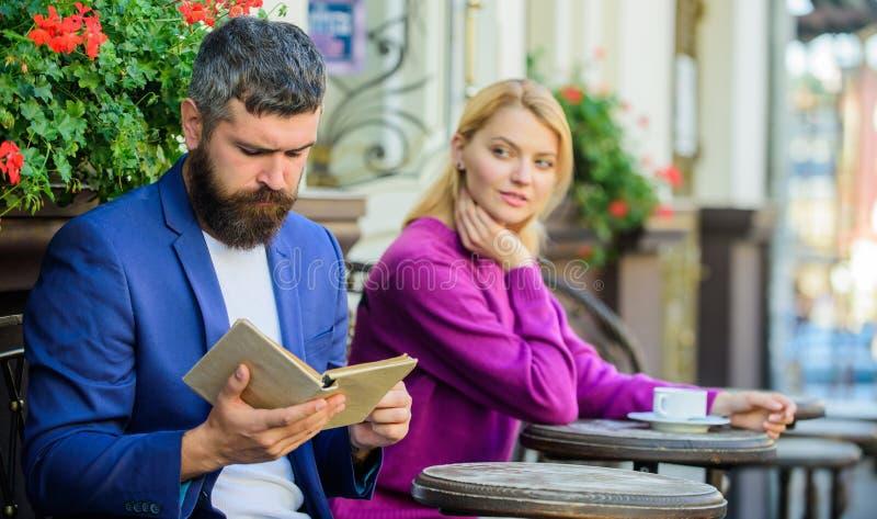 Flört och datum Flickan intresserade vad han läste Möte av folk med liknande intressen Mannen och kvinnan sitter terrassen arkivfoton