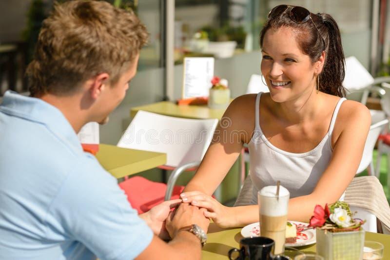 Flörta holdinghänder för par på cafestången royaltyfri foto
