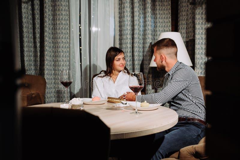 Flörta i ett kafé Härligt älska parsammanträde i ett kafé som tycker om i vin och konversation white för valentin för roman s för royaltyfria foton