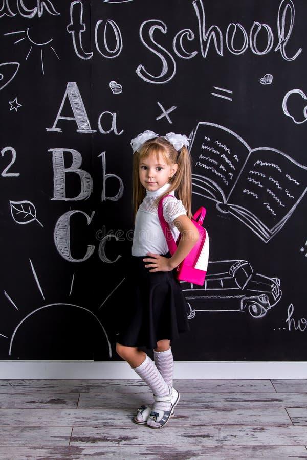 Flörtskolflickaanseende för den svart tavlan som en bakgrund med en ryggsäck på henne tillbaka royaltyfri bild