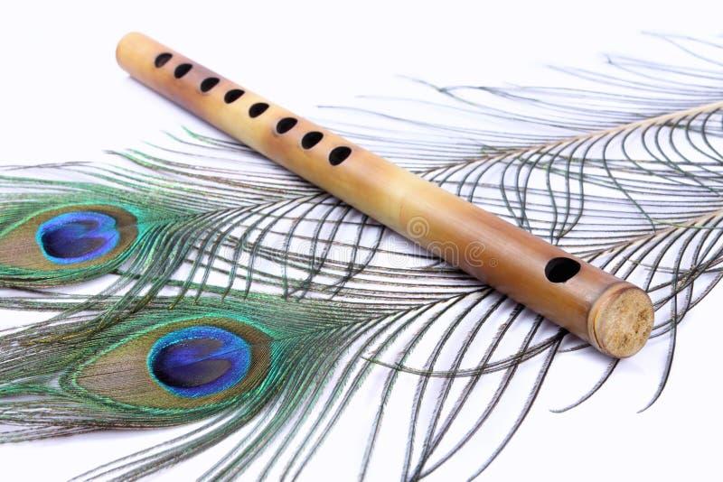 Flöte mit Pfau-Federn lizenzfreies stockfoto
