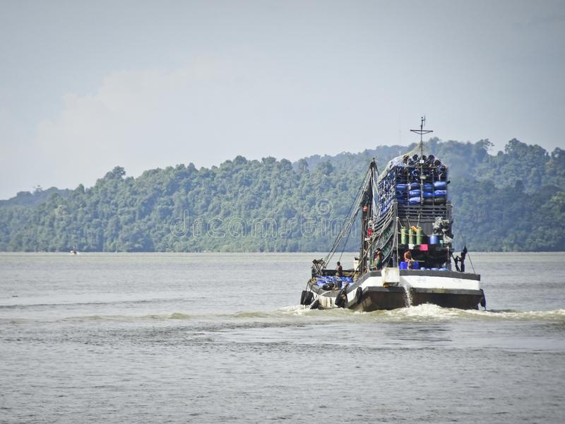 Flöten för lastfartyg på havet laden med trummor av vatten, Thailand arkivfoto