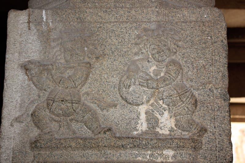 FLÖTEN- und Trommelsäulenschnitzen des männlichen Künstlers Tempels zwei Hampi Vittala Ausführungs stockfoto
