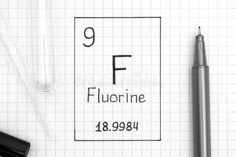 Flúor F del elemento químico de la escritura con la pluma negra, tina de la prueba imagenes de archivo