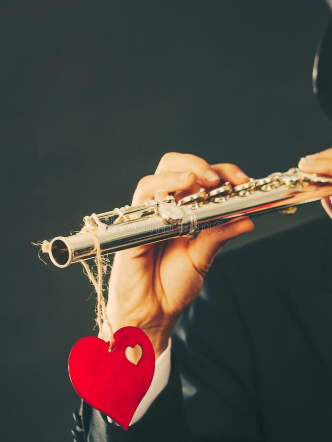 Flûtiste masculin avec la cannelure et le coeur Mélodie d'amour images stock
