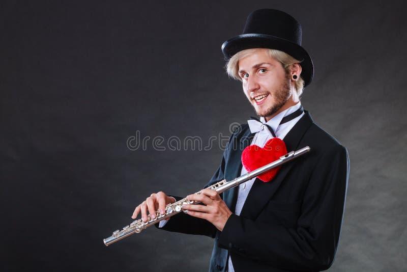 Flûtiste masculin avec la cannelure et le coeur Mélodie d'amour photos stock