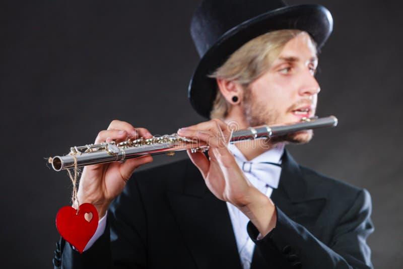 Flûtiste masculin avec la cannelure et le coeur Mélodie d'amour photographie stock