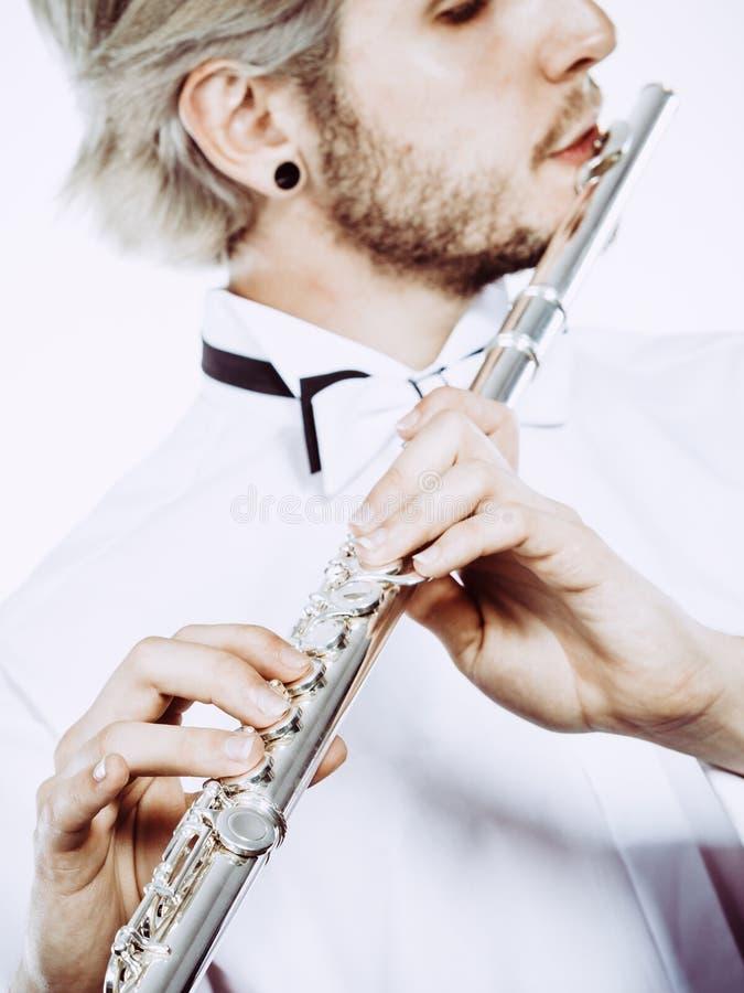 Flûtiste masculin jouant son plan rapproché de cannelure photo libre de droits