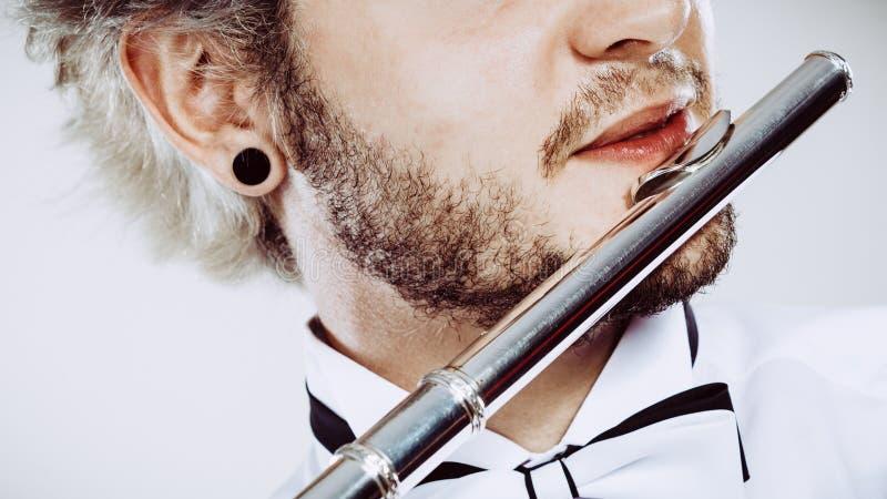 Flûtiste masculin jouant son plan rapproché de cannelure photo stock