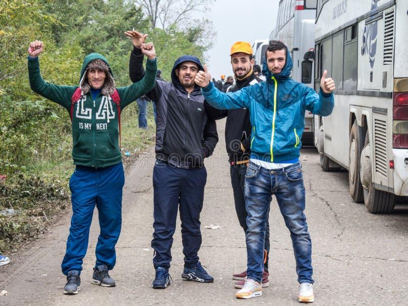 Flüchtlinge, junge Männer von Syrien und Afghanistan, stehend u. werfen vor dem Bus auf, der sie an der Grenze holte stockbilder