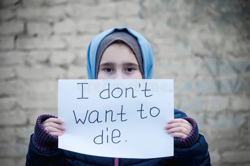 Flüchtlingsmädchen mit einer Aufschrift auf einem weißen Blatt lizenzfreie stockbilder