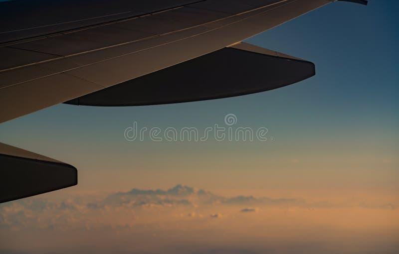 Flügel der Fläche über unscharfer Gebirgsabdeckung mit weißem Schnee Flugzeugfliegen Szenische Ansicht vom Flugzeugfenster Handel lizenzfreie stockfotografie