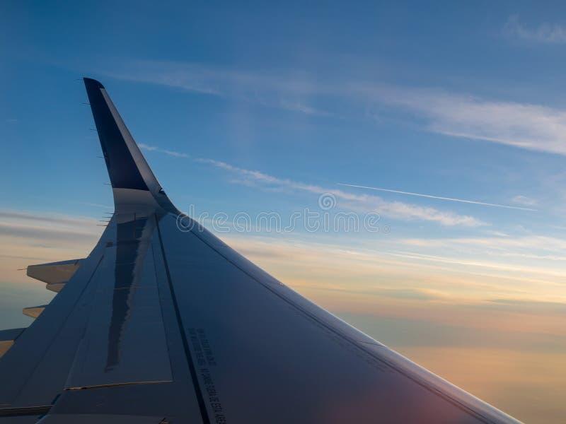 Flügel des Flugzeuges über den Wolken in einem Dämmerungshimmel stockfotos