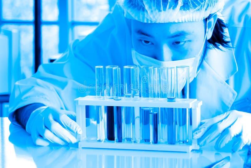 Flüssige Substanz überprüfte durch asiatischen Wissenschaftler oder Chemiker am Labor stockbild