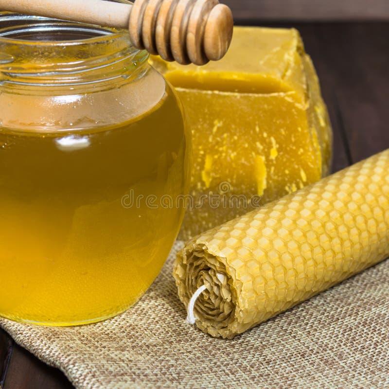 Flüssiger heller Honig mit Löffel und Bienenwachs mit Kerze lizenzfreies stockbild