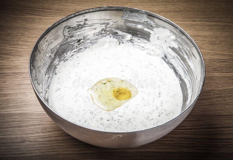 Flüssiger weißer Teig wischen mit Kräutern und einem defekten Ei stockbild