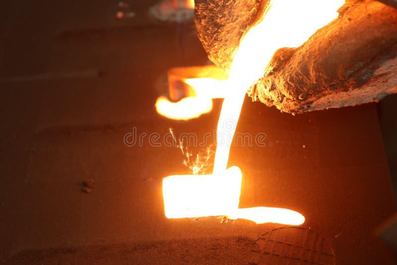 Flüssiges Metall des Eisens, das in Sandförmchen gießt stockfotos