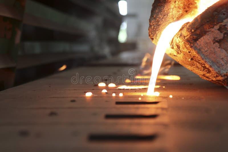 Flüssiges Metall des Eisens, das in Sandförmchen gießt stockfotografie