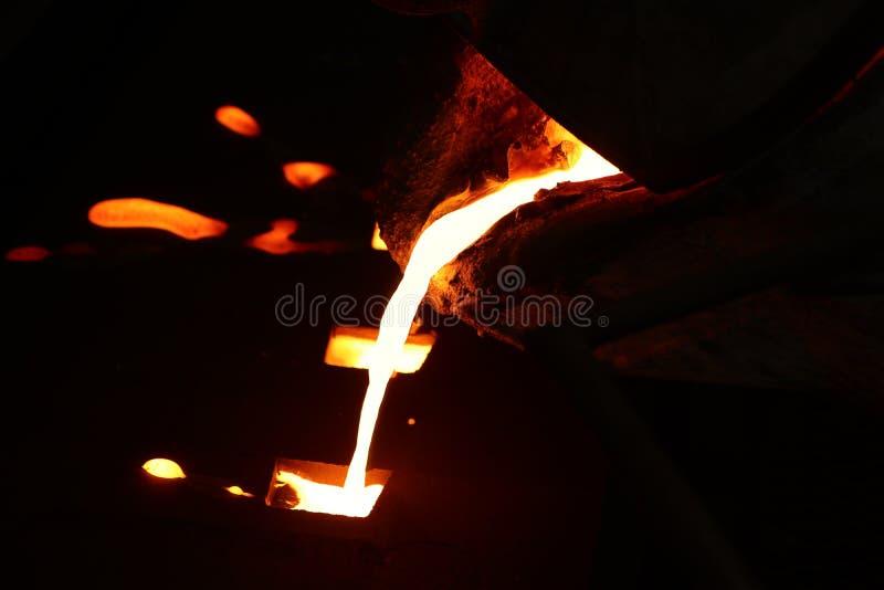 Flüssiges Metall des Eisens, das in Sandförmchen gießt stockbilder