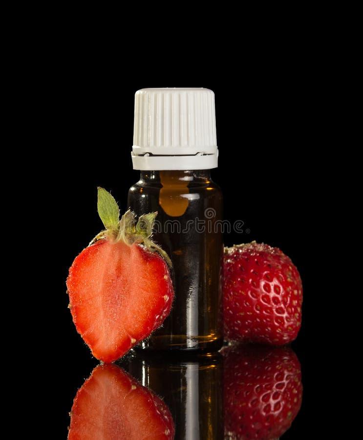 Flüssigkeit für Inhalierungspaare der elektronischen Zigaretten und der Erdbeeren lokalisiert auf Schwarzem lizenzfreies stockbild