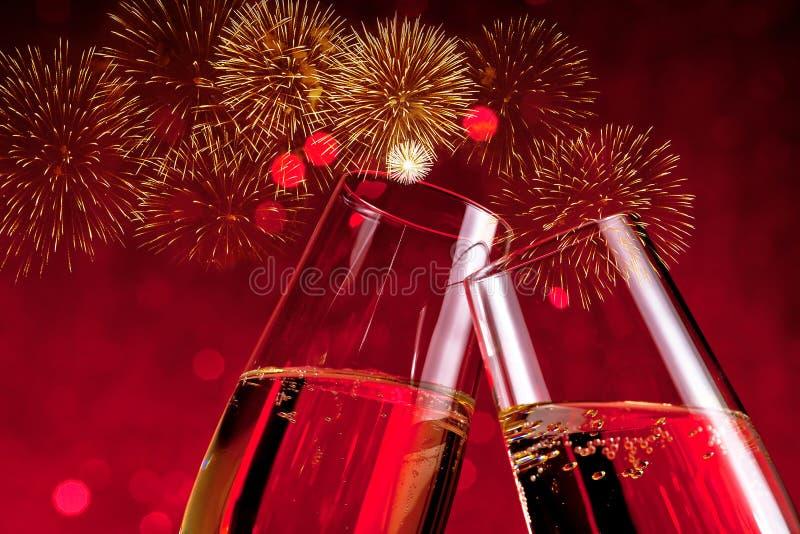 Flûte con le bolle dorate sul bokeh della luce rossa e sul fondo della scintilla dei fuochi d'artificio fotografia stock libera da diritti