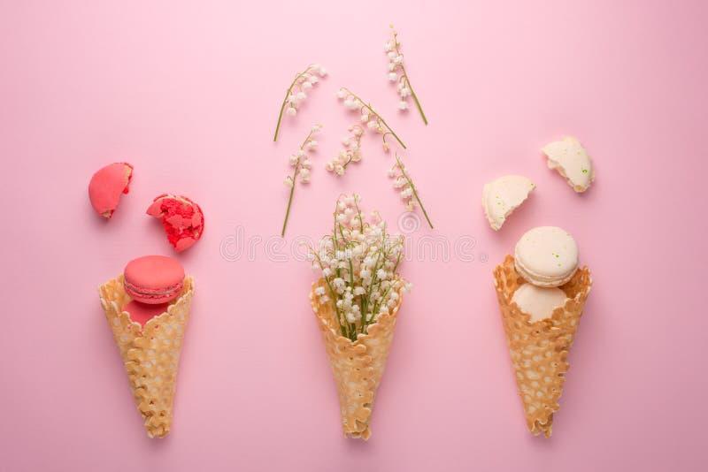 Flach-Lage eines süßen Kegels der Oblaten mit weißen Blumen und Makronen über einem hellrosa Pastellhintergrund, Draufsicht Das K stockfotos