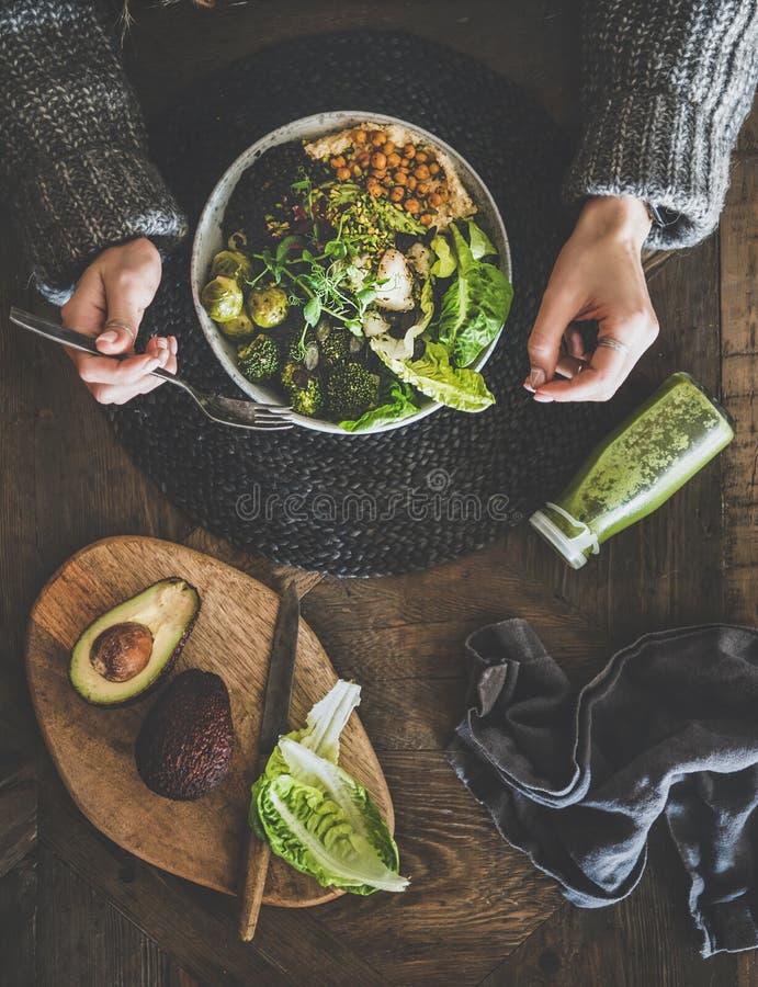 Flach-Lage gesundes Abendessen vegetarischen superbowl, Smoothie- und Frauenhände lizenzfreie stockfotografie