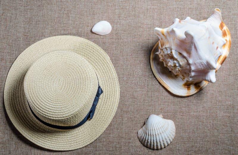 Flache Ansicht der Ferien mit Strohhut und Meershellssea Oberteilen lizenzfreie stockfotografie