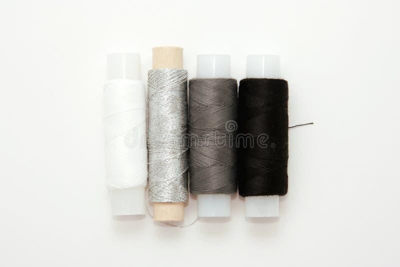 Flache gelegte bunte Baumwollfadenspulen, Stickerei weiß, grau, schwarz, silbern, Spulen, Spott oben, Draufsicht Planmodellfreier stockfotos