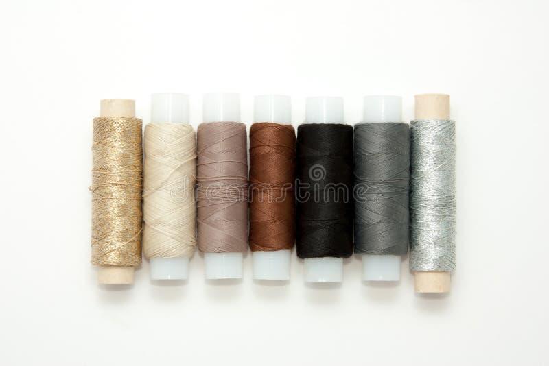 Flache gelegte bunte Baumwollfadenspulen, Stickgarn, weiß, braun, grau, schwarz, silbern, Goldspulen, Schein oben, Draufsicht stockfotos