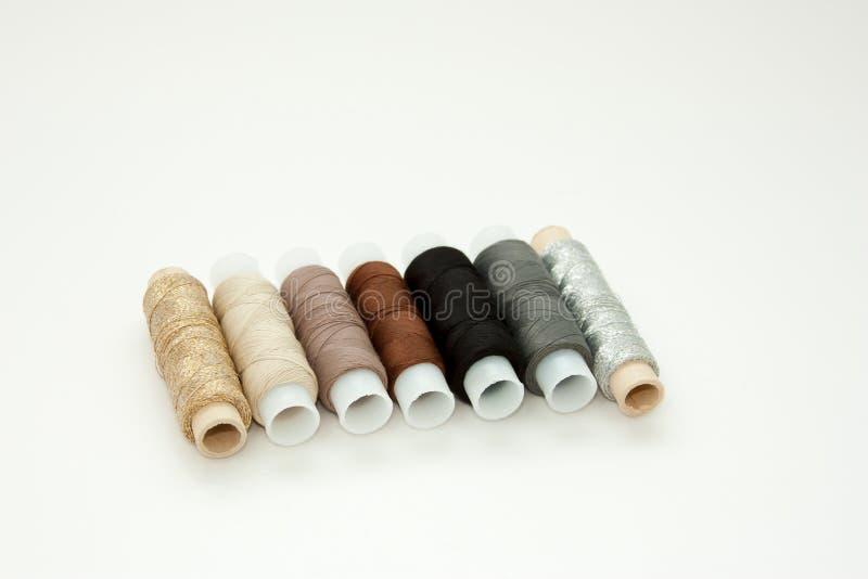 Flache gelegte bunte Baumwollfadenspulen, Stickgarn, wei?, braun, grau, schwarz, silbern, Goldspulen, Schein oben, Draufsicht lizenzfreies stockfoto