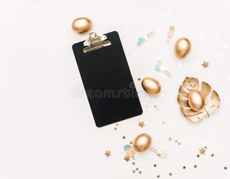 Flache gelegte Gold-Ostereier mit Dekorationen auf weißem Hintergrund stockfotografie