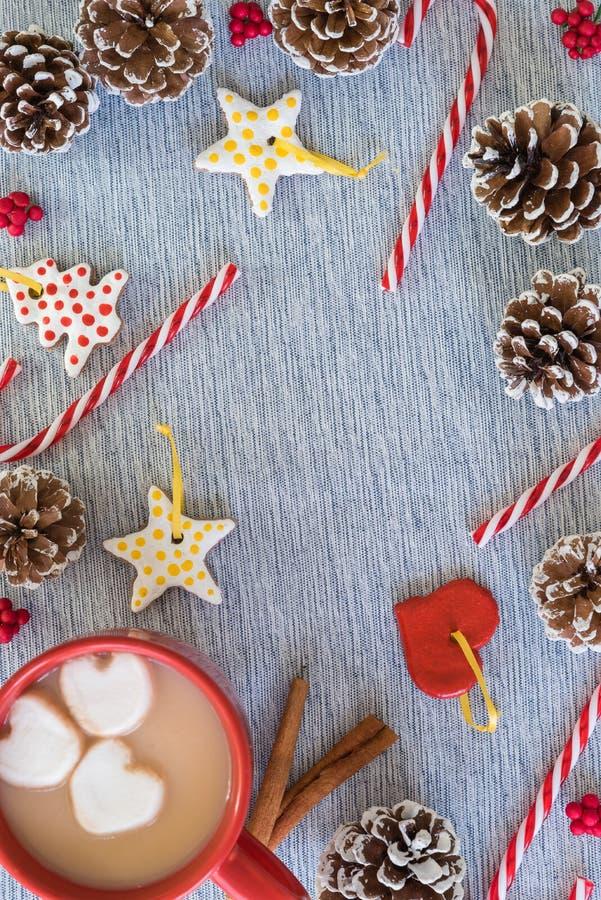 Flache gelegte Weihnachtsgrenze mit Becher heißem Kakao, Zuckerstangen, pinecones lizenzfreies stockbild