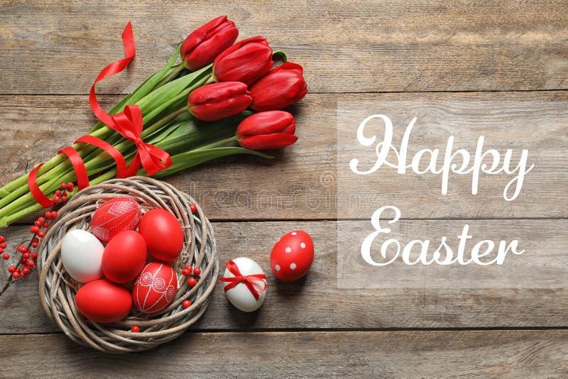 Flache gelegte Zusammensetzung des Nestes mit gemalten Eiern und Text fröhliche Ostern stockfoto