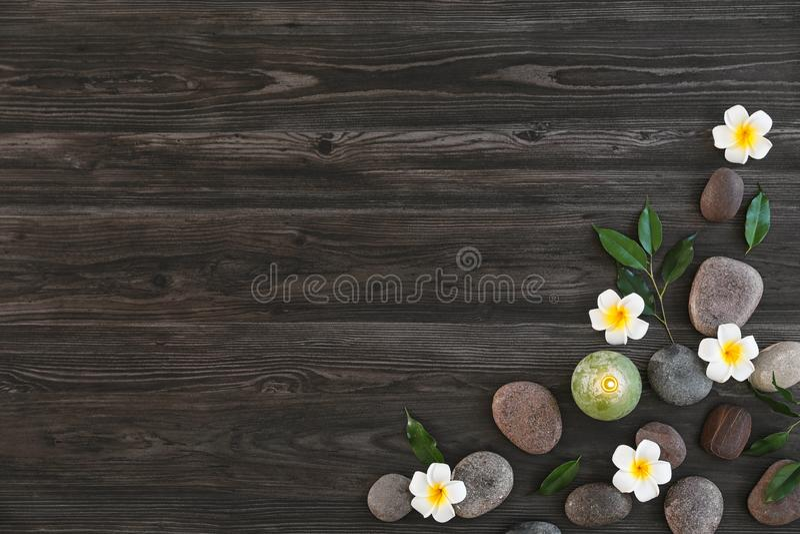 Flache gelegte Zusammensetzung mit Badekurortsteinen, -blumen und -kerze auf hölzernem Hintergrund lizenzfreie stockfotos