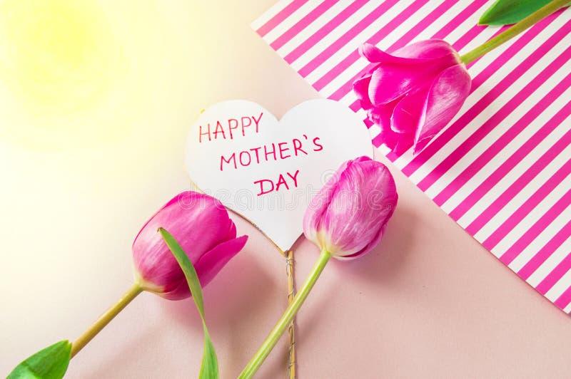 Flache gelegte Zusammensetzung mit Blumen und Herz für mother' s-Tag, grüßend für Frauen Rote Tulpen auf rosa Hintergrund stockbild