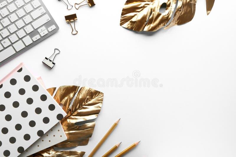 Flache gelegte Zusammensetzung mit Computertastatur, goldenen tropischen Blättern und Zusätzen auf weißem Hintergrund lizenzfreie stockbilder