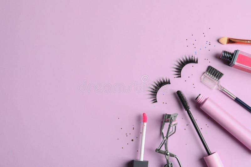 Flache gelegte Zusammensetzung mit den falschen Wimpern und anderen kosmetischen Produkten auf rosa Hintergrund, Raum lizenzfreies stockbild