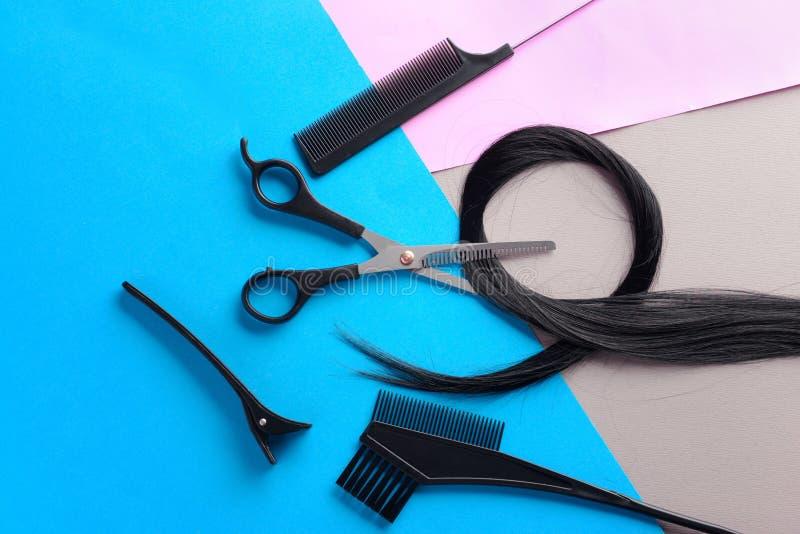 Flache gelegte Zusammensetzung mit den Werkzeugen und dem Strang des Friseurs des schwarzen Haares auf Farbhintergrund stockbild
