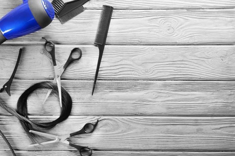 Flache gelegte Zusammensetzung mit den Werkzeugen und dem Strang des Friseurs des schwarzen Haares auf hölzernem Hintergrund stockbilder