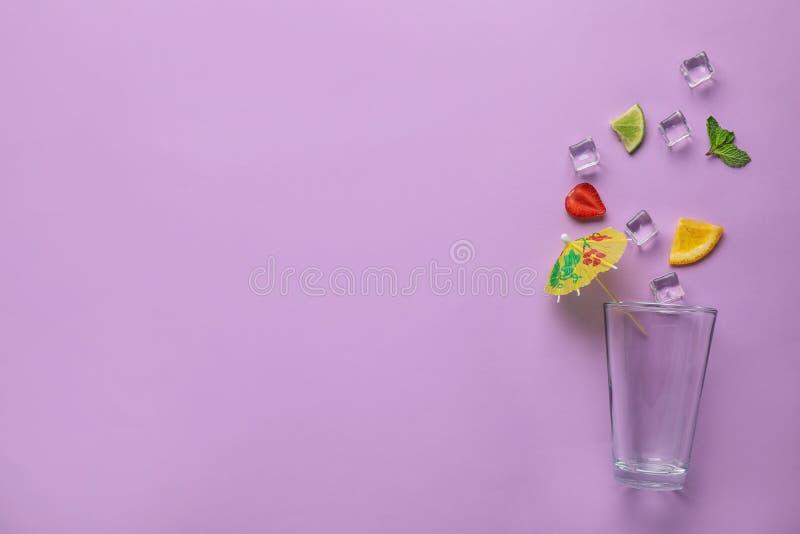 Flache gelegte Zusammensetzung mit Glas, Eis und geschnittenen Früchten auf Farbhintergrund Sommer-Cocktail-Rezept lizenzfreie stockfotografie