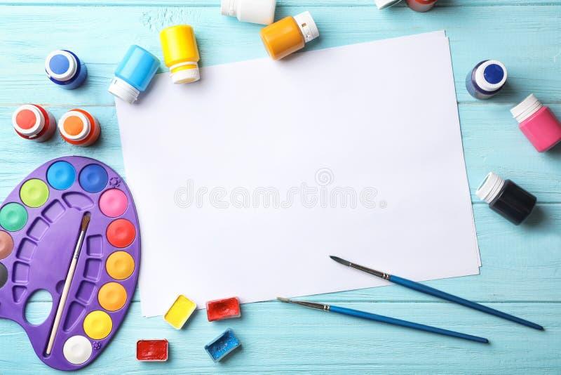 Flache gelegte Zusammensetzung mit leerem Papier und malende Versorgungen für Kind auf Tabelle stockfotos