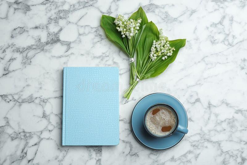 Flache gelegte Zusammensetzung mit Notizbuch, Maigl?ckchenblumenstr?u?en und Kaffee auf Marmorhintergrund stockfoto