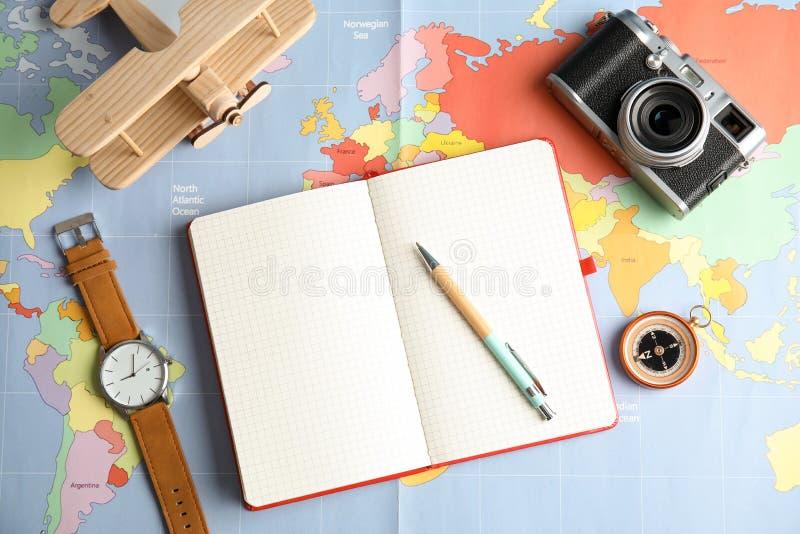 Flache gelegte Zusammensetzung mit Notizbuch und Kamera auf Weltkarte, Raum für Text stockfotos