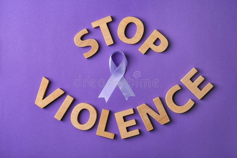 Flache gelegte Zusammensetzung mit purpurrotem Band und Wörter STOPPEN GEWALTTÄTIGKEIT auf violettem Hintergrund lizenzfreie stockfotos