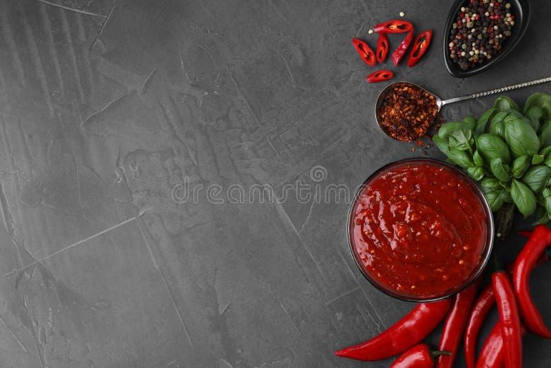 Flache gelegte Zusammensetzung mit Schüssel Chili-Sauce und Bestandteilen auf grauer Tabelle stockfotografie
