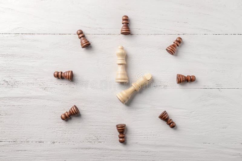 Flache gelegte Zusammensetzung mit Schachfiguren auf weißem hölzernem Hintergrund stockfotografie