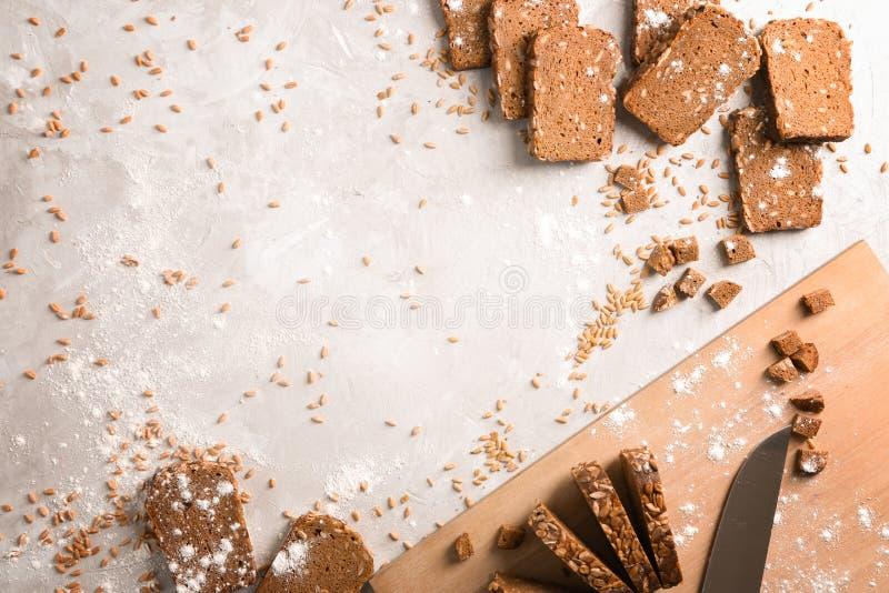 Flache gelegte Zusammensetzung mit Scheiben des frisch gebackenen Roggenbrotes auf grauem Hintergrund lizenzfreie stockbilder